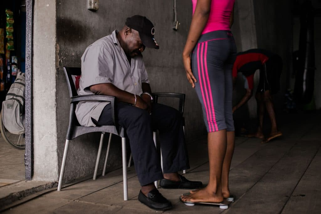 11 July 2019: After each training session, Coach Adeboyega checks the weight of the boxers to monitor their progress, Lagos, Nigeria